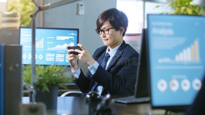 东亚商人Plaing电子游戏的射击在他的Sm的 免版税库存图片