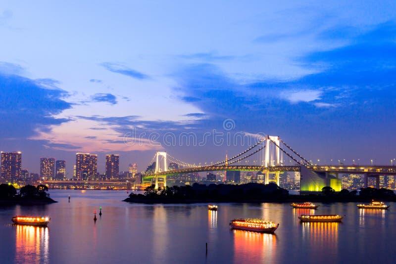 东京地平线日落微明,与都市风景和彩虹Bri 免版税库存图片