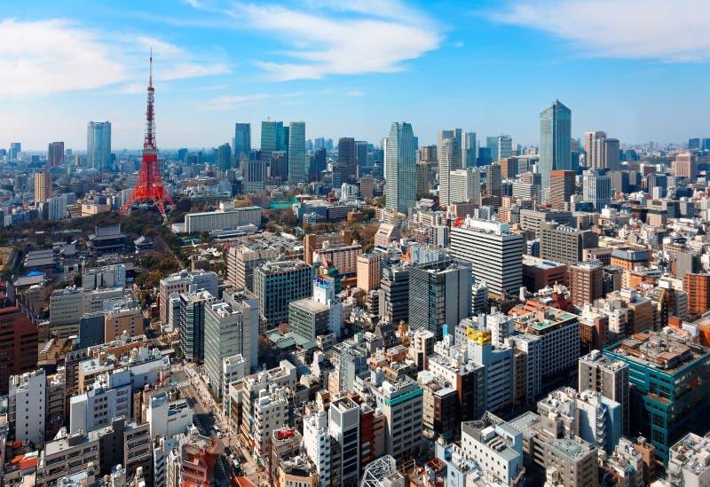 东京市美好的都市地平线在蓝色晴朗的天空下,当东京铁塔站立高在拥挤高层摩天大楼中 免版税库存照片