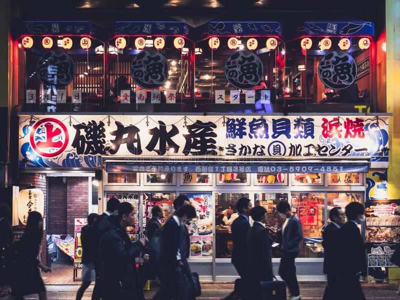 东京日本- 2018年4月17日:新宿地区餐馆商店吃并且喝日本薪金人走的东京夜生活 免版税库存照片