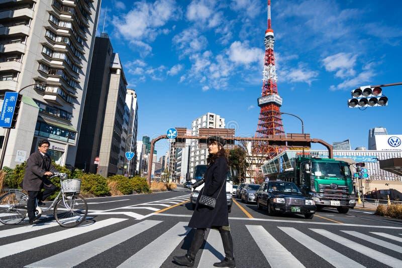 东京,日本- 2018年12月25日:走横跨在东京铁塔前面的街道的人们美丽的多云天空蔚蓝的 库存图片