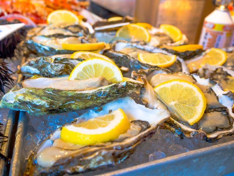 东京,日本2017年6月28日- :与柠檬片断的蛤蜊在鱼市Tsukiji批发的待售在东京日本 免版税库存照片