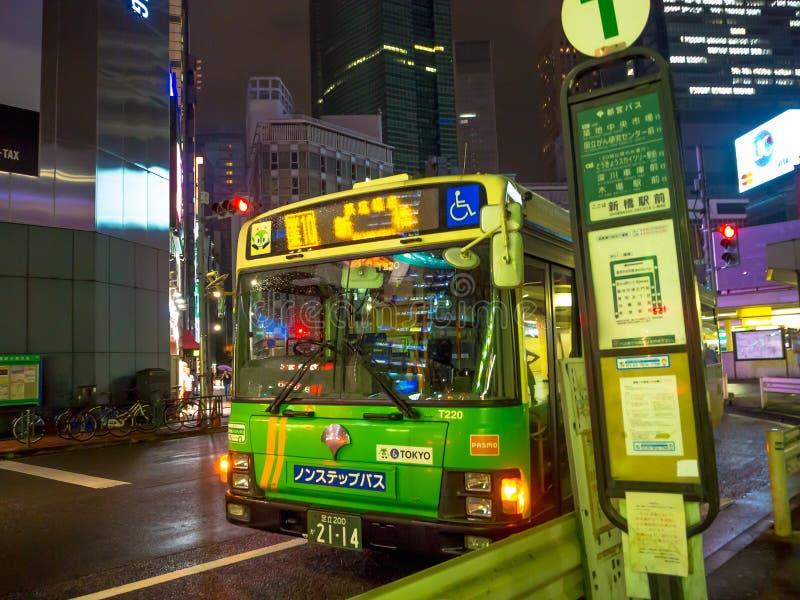 东京,日本2017年6月28日- :公车运送等在公共汽车站人在街道在新宿金黄盖氏,位于东京 免版税库存图片