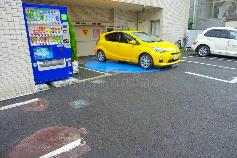 东京,日本2017年6月-28 :汽车停放了近汁液自动贩卖机和停车场自动售货机米人的 免版税库存图片
