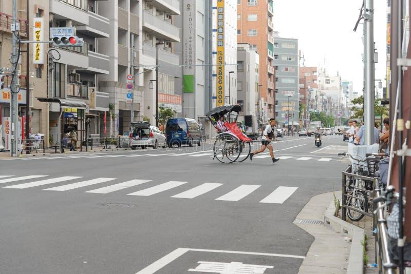 东京, JAPAN-JULY 2018年:司机运载的游人驾驶的著名richshaws在Senso籍寺庙附近 库存图片