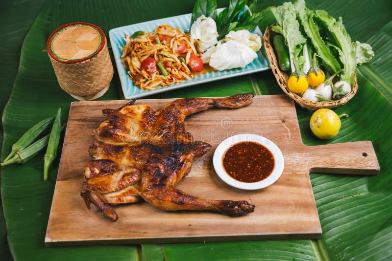 东南亚和东亚:典型的亚洲菜,盘中供应的番木瓜沙拉烤鸡,泰国东北菜风格 库存照片