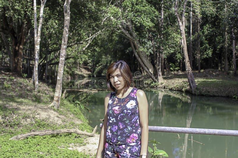 东南亚国家联盟妇女和水在小河是绿色的,并且鲜绿色的树在卡普瀑布前面在泰国停放,Chumphon 图库摄影