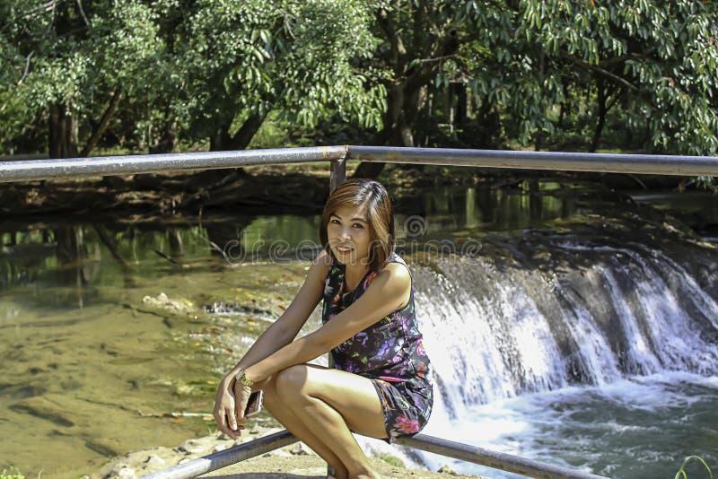 东南亚国家联盟妇女和水在小河是绿色的,并且鲜绿色的树在卡普瀑布前面在泰国停放,Chumphon 库存图片