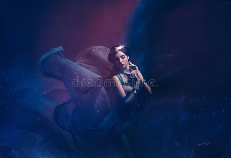 东方服装的一个女孩,风暴的女王/王后 Jasmine公主 背景是转弯和一阵强风 工作室 库存照片