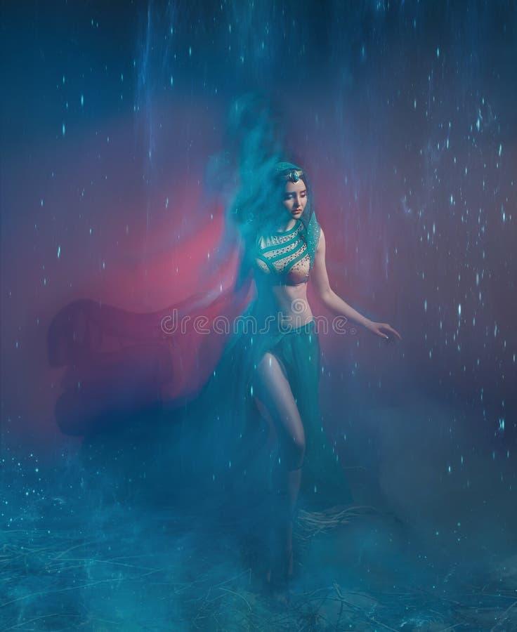 东方服装的一个女孩,风暴的女王/王后 Jasmine公主 背景是转弯和一阵强风 工作室 图库摄影