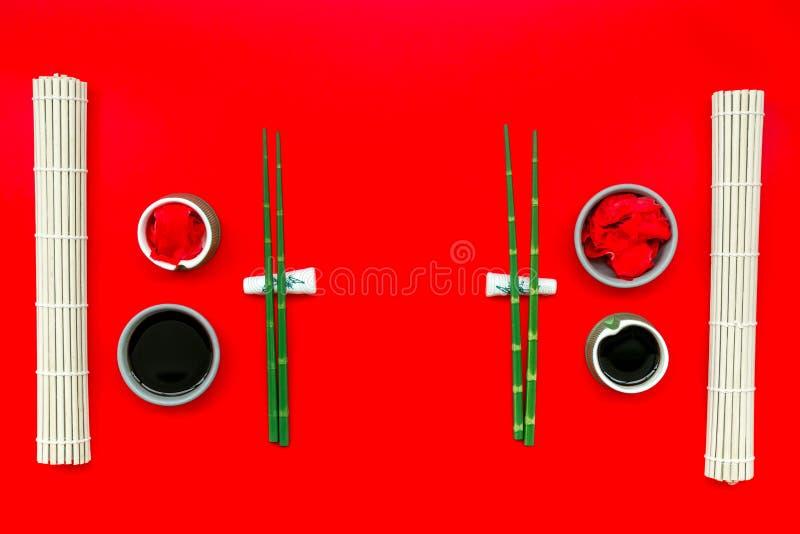 东方桌设定用寿司和maki的,在红色背景顶视图的酱油竹棍子 免版税库存图片