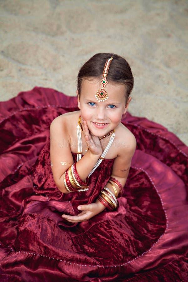 东方衣物的女孩坐沙子 免版税库存照片