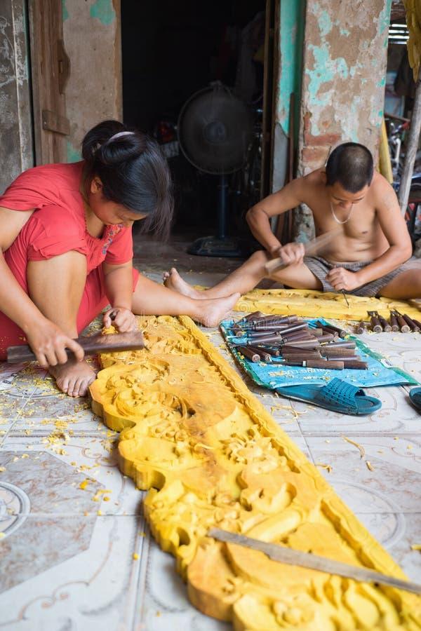 东Anh,河内,越南- 2015年9月20日:做木头雕刻在他们的房子前面的一个人和他的妻子在Dao Thuc村庄产品 库存照片