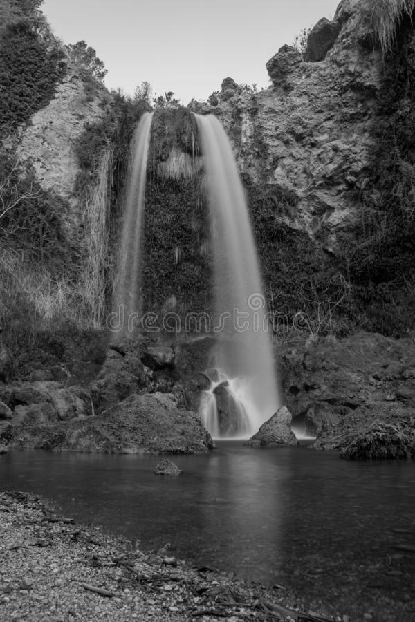 丝绸水 黑白瀑布 瀑布在流经树的森林风景长的曝光和在黑色的岩石 免版税库存图片