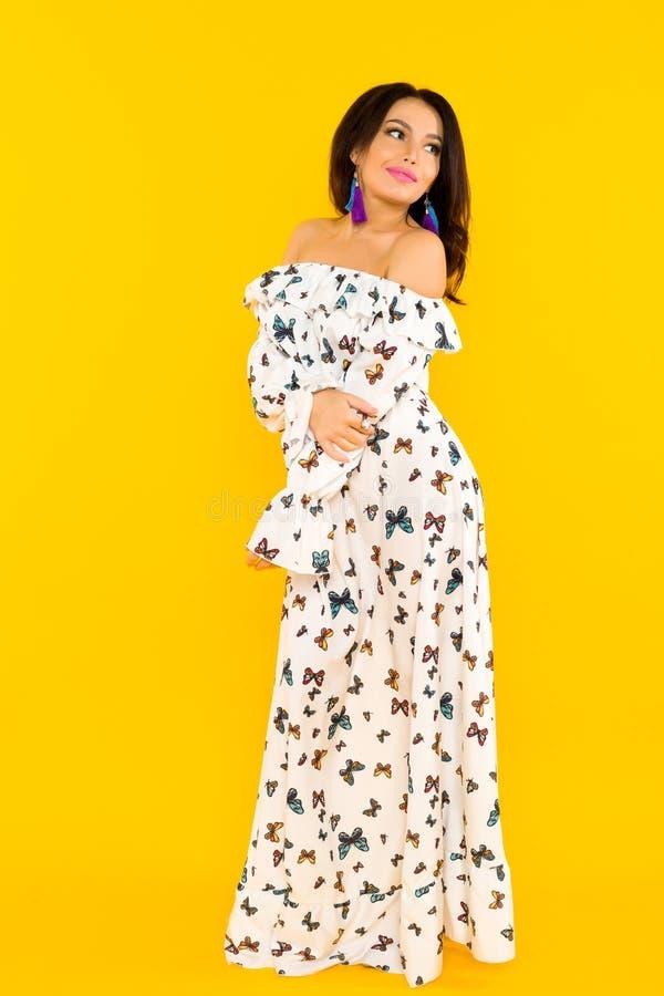 丝绸礼服的逗人喜爱的亚裔妇女有摆在黄色背景的蝴蝶的 库存照片