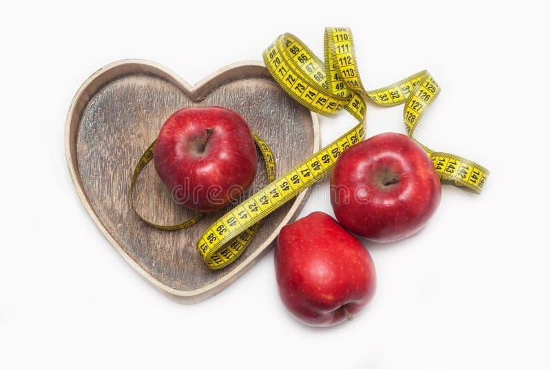 丢失称 关闭测量在红色苹果附近的黄色磁带领带在木心脏形状箱子 背景查出的白色 Hori 免版税库存图片