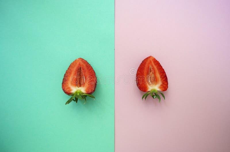 两一半在桃红色和绿松石背景的草莓 库存照片