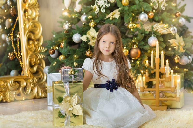 两一女孩姐妹画象接近白色绿色圣诞树的 美丽的晚礼服的女孩在新穿衣 库存照片