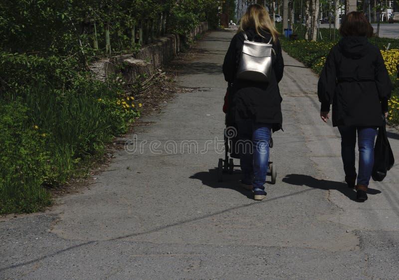 两一起走的女孩 跑在春天的两个愉快的爱装饰的女孩走,后面看法,友谊概念 图库摄影