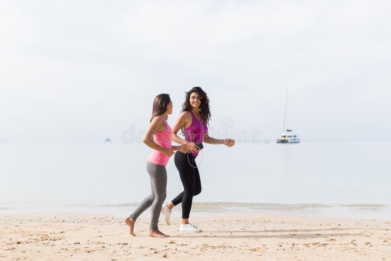 两一起跑沿沿海亭亭玉立的女孩的少妇跑步在海滩女性体育赛跑者健身训练 免版税库存图片
