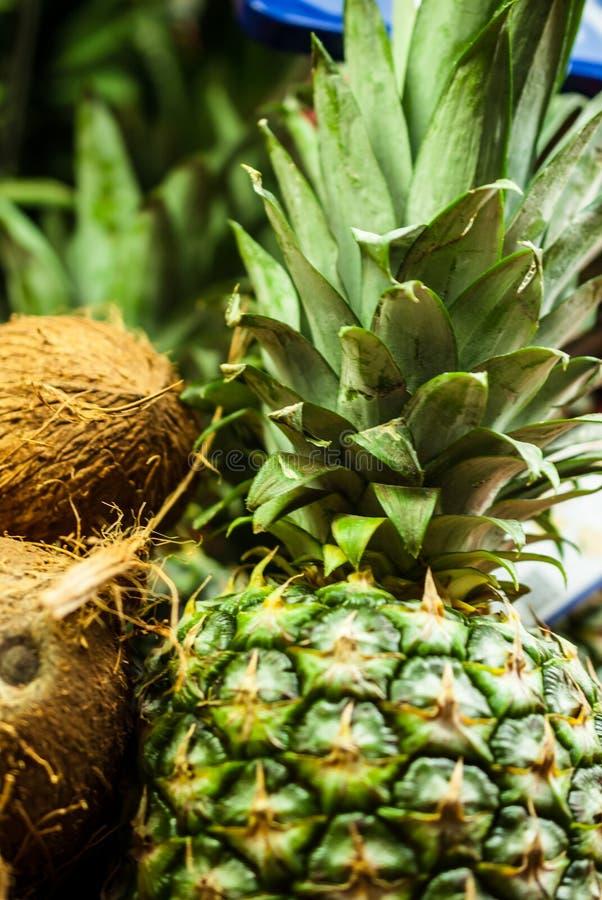 两三个椰子和菠萝在一个商店窗口里在商店特写镜头 免版税库存图片