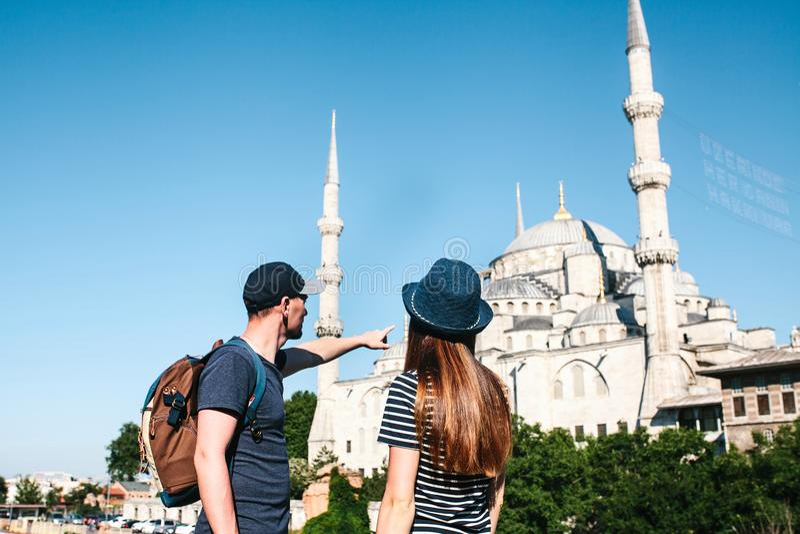两三个游人一个年轻人和一名俏丽的妇女在举世闻名的蓝色清真寺也叫的Sultanahmet旁边站立 免版税库存照片