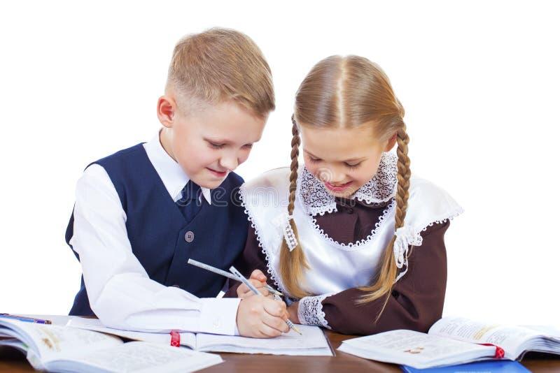 两三名小学学生坐在书桌 免版税库存照片