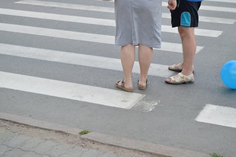 两三更老的站立在行人穿越道和谈的男人和妇女 库存图片