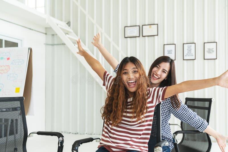 两不同种族的年轻创造性的配合获得坐的乐趣笑,微笑和在办公室椅子 庆祝为的工友妇女 免版税库存图片