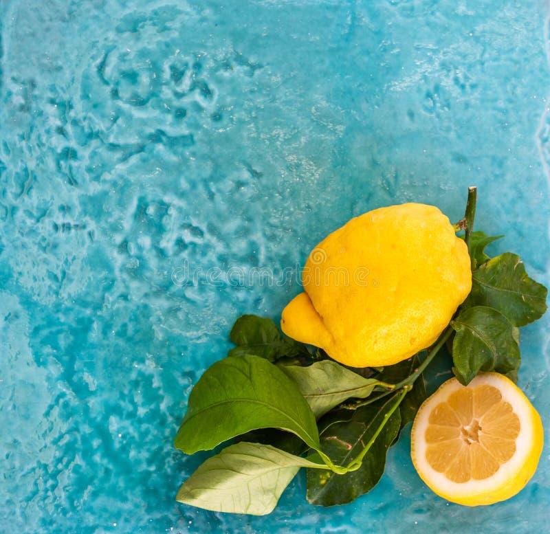 两与叶子的新鲜的柠檬蓝色陶瓷表面上 顶视图 库存照片