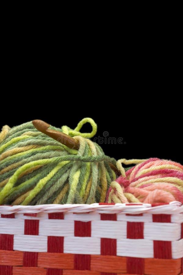 两与桃红色和绿色混合物毛线羊毛球,在黑背景隔绝的木自然竹钩针照片的红色 前面 库存图片