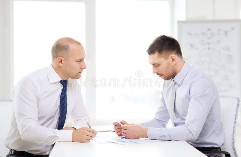 两与纸的严肃的商人在办公室 免版税图库摄影