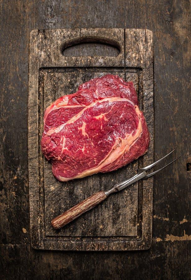 两与肉叉子的未加工的牛肉ribeye牛排在黑暗的土气木毁坏的委员会 库存图片
