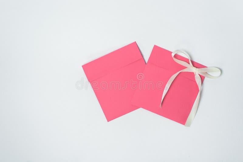 两与黄色丝带的红色信封以CD,方形的信封的一把弓的形式 免版税库存图片