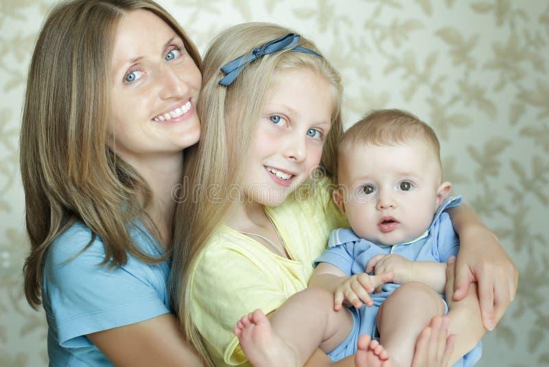 两世代愉快的母亲家庭画象有两可爱的兄弟姐妹的 免版税库存照片