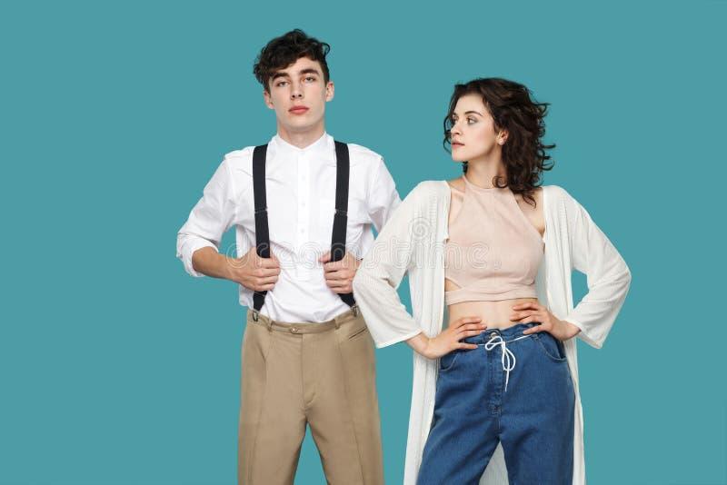两严肃的骄傲的深色的时髦的伙伴或夫妇身分,在腰部的手画象,看以确信 ??  图库摄影