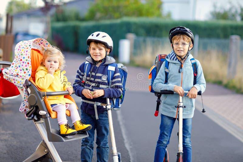 两个一点学校孩子的男孩和去逗人喜爱的小孩的女孩教育 坐在摇篮车的微小的儿童姐妹 乘坐的兄弟  免版税图库摄影