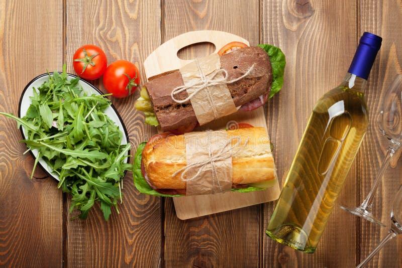 两个三明治、沙拉和白葡萄酒 库存照片