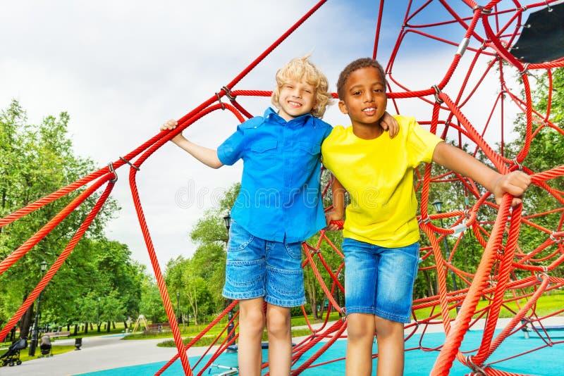 两个不同的看的男孩站立接近在红色网 免版税图库摄影