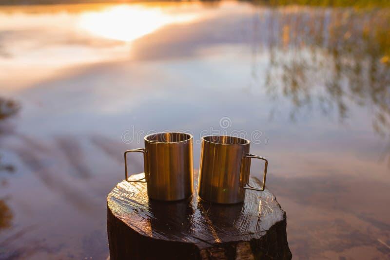 两个不锈钢野营的杯子或杯子在一个木树桩反对剧烈的日出或阳光由湖 野营的概念 图库摄影