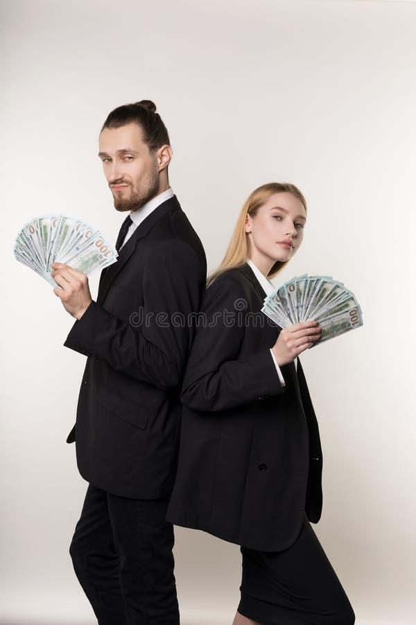两个严肃的商务伙伴英俊的有胡子的紧接站立与金钱的人和美丽的白肤金发的女孩在手上 库存图片