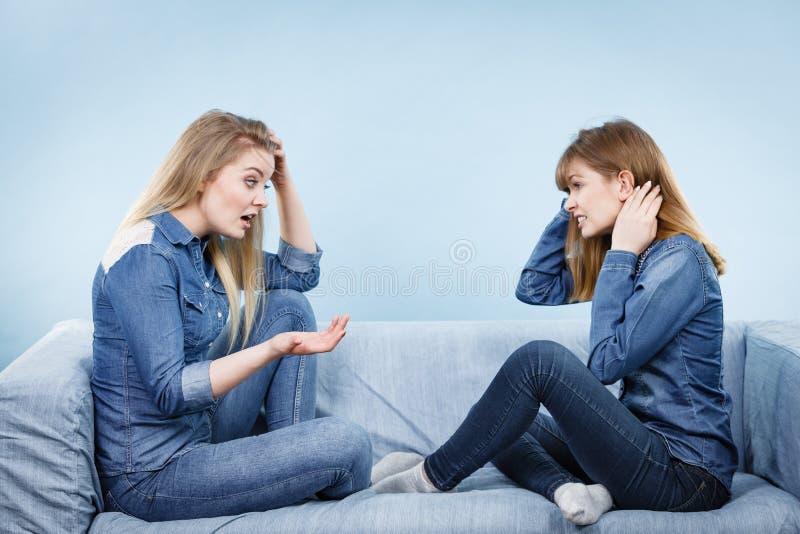 两个严肃的妇女朋友谈话在沙发 免版税库存图片