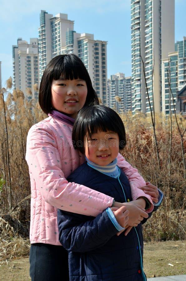 两个中国青少年的姐妹拥抱上海中国 免版税库存照片