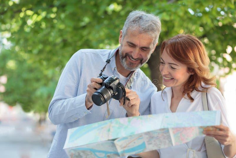两个中间成人游人走通过公园的,妇女拿着一张地图,并且人显示在数码相机的图片 免版税图库摄影