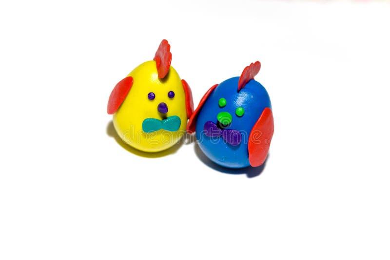 两个五颜六色的花鸡蛋被做以小彩色塑泥鸡的形式 鸡在伟大的复活节的天被做 库存图片