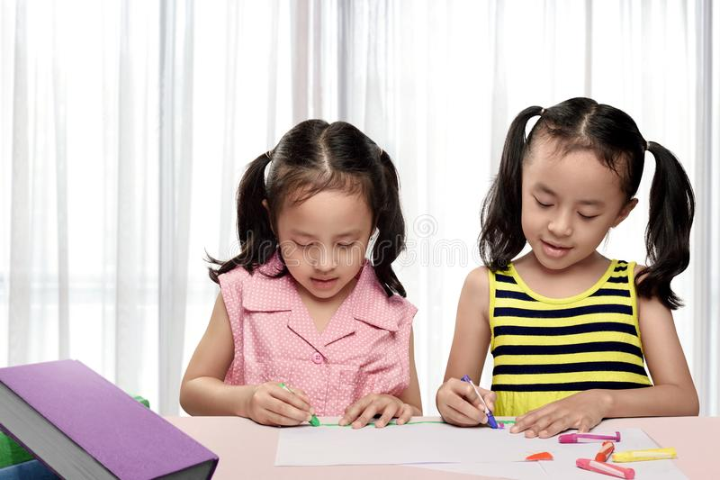 两个亚洲人与五颜六色的蜡笔的女孩图画 免版税库存照片