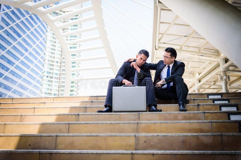两个亚洲人商人感受哀伤和沮丧的翻倒无法在生活中 免版税库存图片