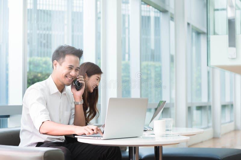 两个亚洲工友用途膝上型计算机工作一起 免版税库存图片