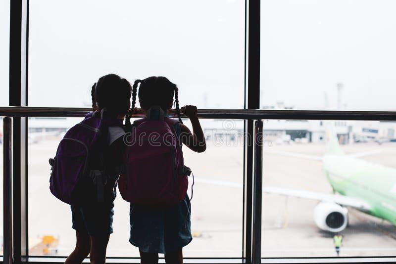 两个亚裔儿童女孩剪影有看飞机和等待搭乘的背包的在机场 免版税库存照片
