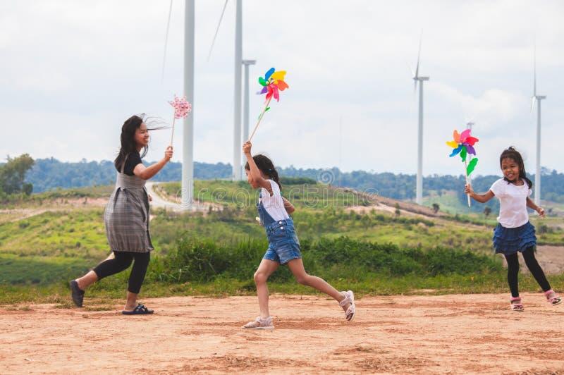 两个亚裔儿童女孩和他们的母亲是一起跑和使用与风轮机玩具在风轮机领域 库存照片
